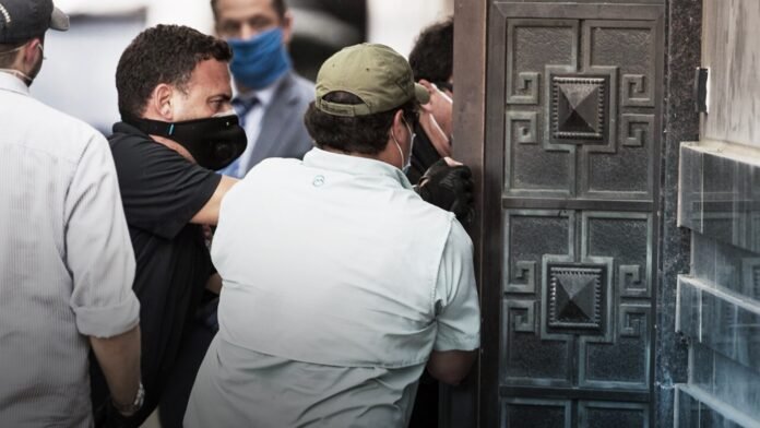 Federal officials and a locksmith pull on a door to make entry into the vacated Consulate General of China building Friday, July 24, 2020, in Houston.